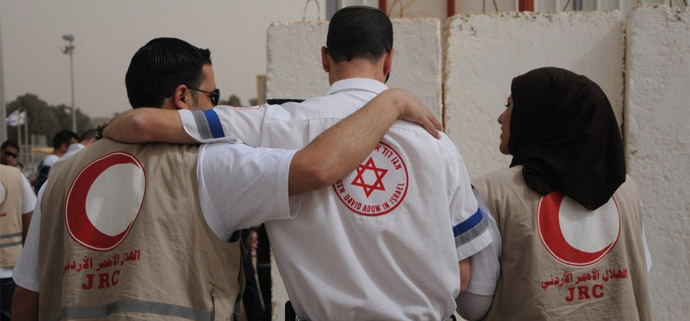 A medic from Magen David Adom walking with his counterparts from the Red Crescent